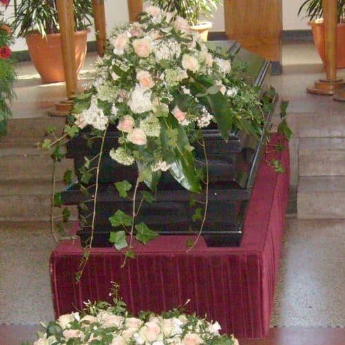Sargdekoration-mit-rosa-Blumen