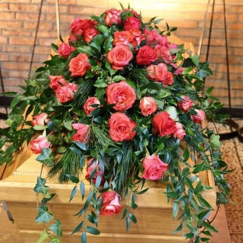Sargdekoration-mit-rote-Rosen